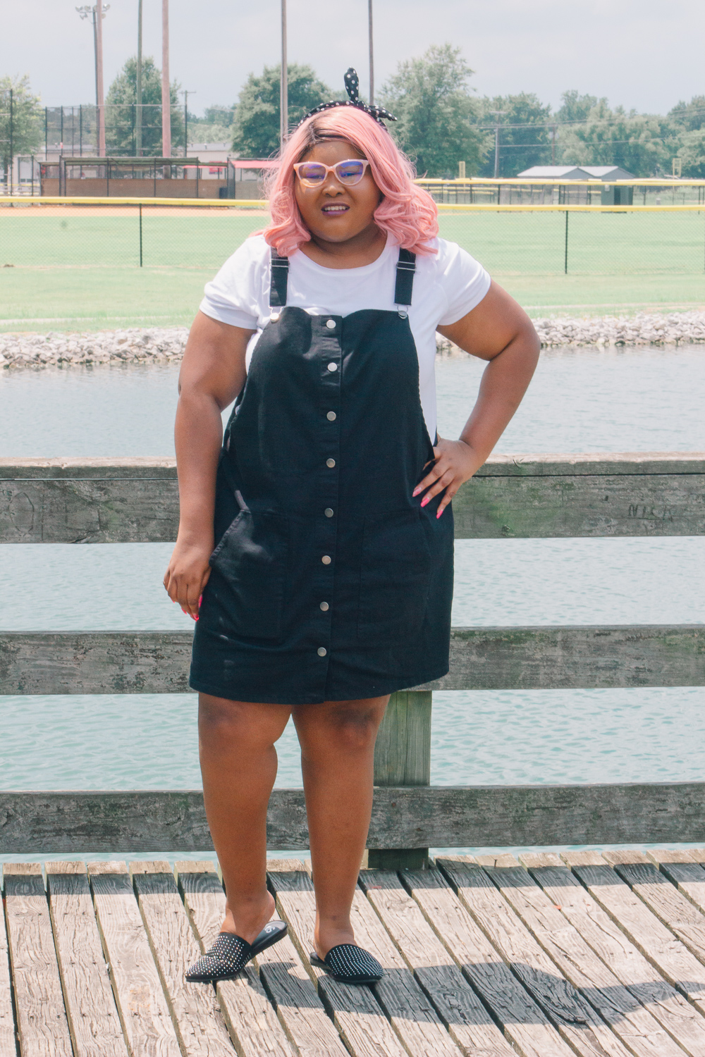 Styling SO in the park. Amanda is wearing a black polka dot headband, a white shirt, a black pinafore, and black mules.